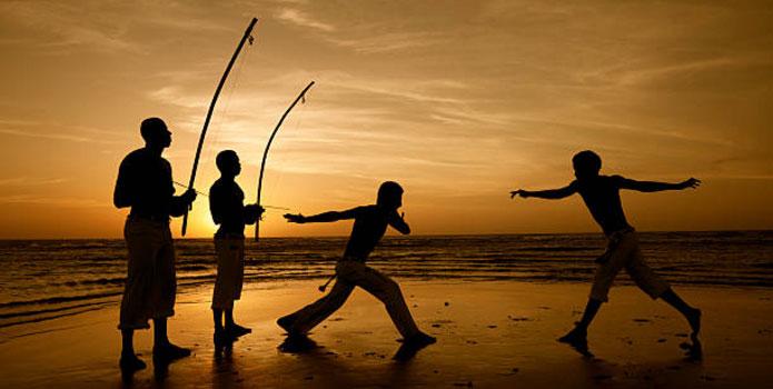 Danseurs de capoeira sur la plage avec musiciens