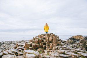 personne en cirée vue de dos sur les rochers en Irlande
